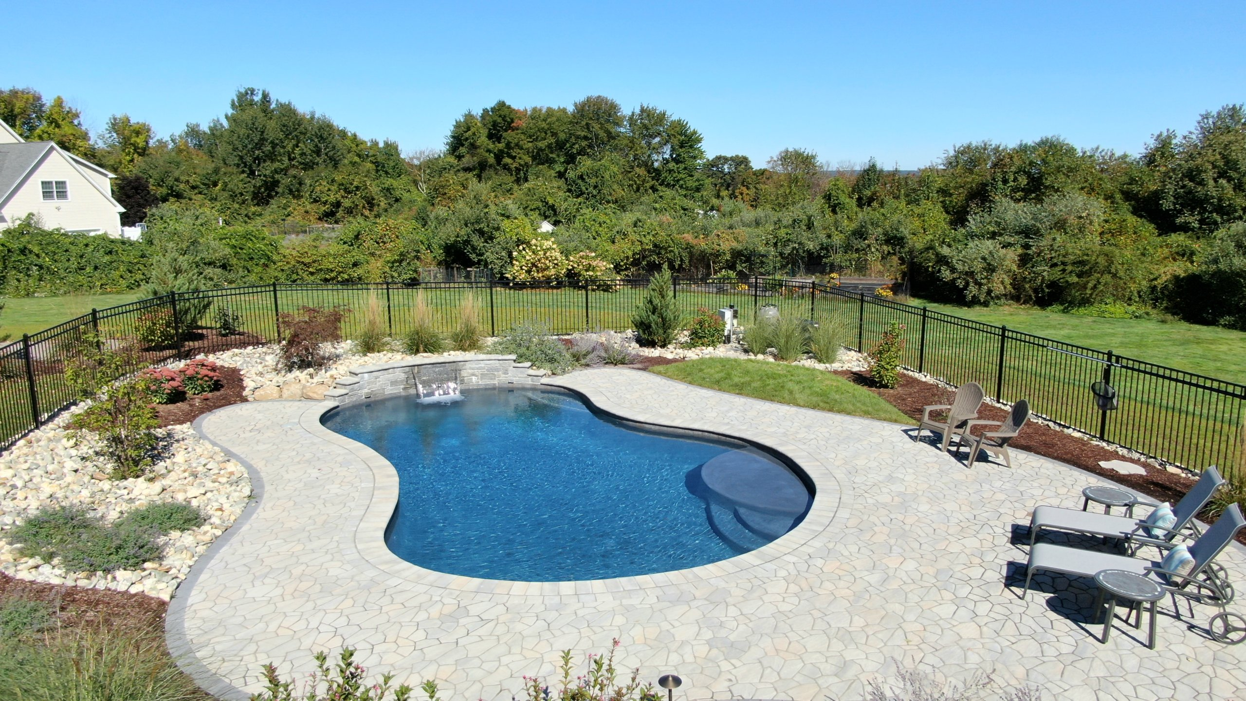 inground gunite pool with patio and waterfall